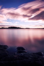 Purple sunset, white clouds in the sky, lake water iPhone wallpaper