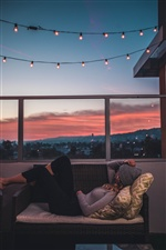 Girl, rest, sofa, balcony, holiday lights iPhone wallpaper